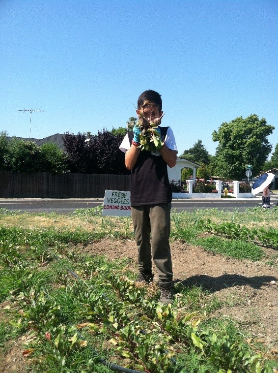 Nico shows off the beets he harvested.