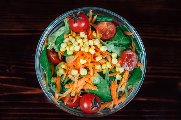 Salad with corn, tomato, lettuce, carrot and spinach