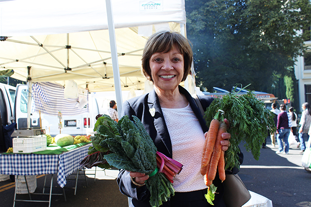 Karen Ross holding bundle of carrots and chard at farmers market